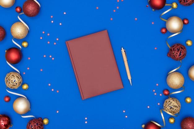 Piatto di natale laici con decorazioni e taccuino e penna su carta blu
