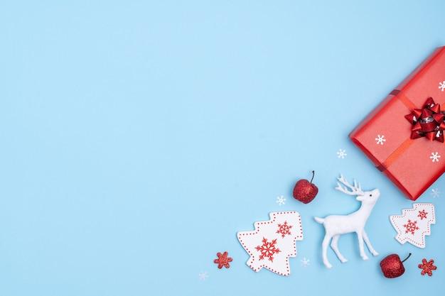 Piatto di natale laici con confezione regalo, stelle, albero di natale e cervi su carta blu pastello