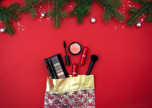 Piatto di natale con prodotti cosmetici per il trucco in sacchetto regalo su sfondo rosso vista dall'alto