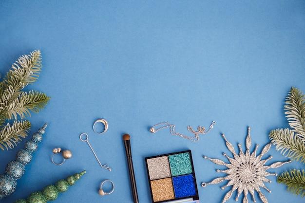Piatto di natale con laici con cosmetici e gioielli in argento, sfondo blu, copia dello spazio