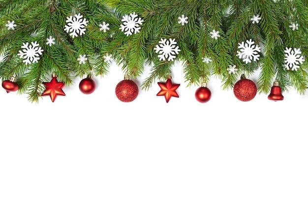 Natale piattamente copyspace. rami di abete rosso su sfondo bianco isolato. giocattoli rossi di natale, palle. decorazione natalizia.
