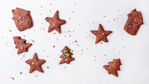 Sfondo di cibo di natale con pasta frolla al cioccolato tagliata a forma di alberi di natale, stelle e case.