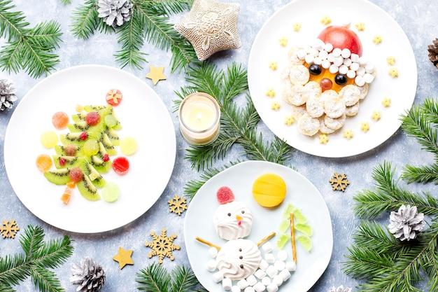 Cibo natalizio per bambini: albero di natale con kiwi, pupazzo di neve marshmallow, babbo natale con banana. vista dall'alto