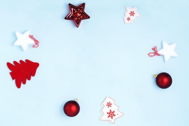 Composizione nella cornice di natale con i giocattoli di natale sul blu pastello