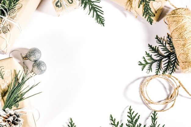 Composizione in cornice di natale con rami di thuja, pigne, regali confezionati artigianalmente e ornamenti festivi su sfondo bianco. vista dall'alto, distesa piatta con spazio per le copie.