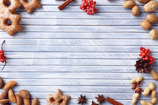 Cornice natalizia di biscotti, noci e spezie su fondo in legno colorato