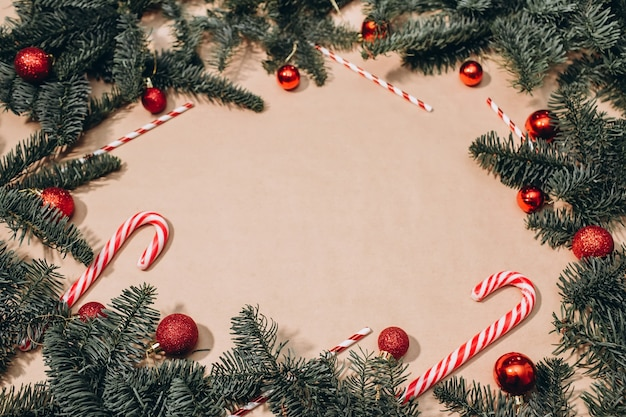 Cornice natalizia di rami di abete, palline rosse, bastoncini di liquirizia, ghirlande