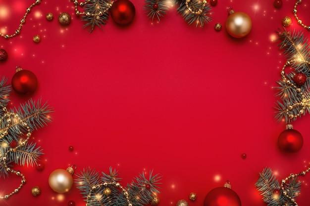 Cornice natalizia di ghirlanda di abeti, decorazioni in oro su sfondo rosso spazio copia.