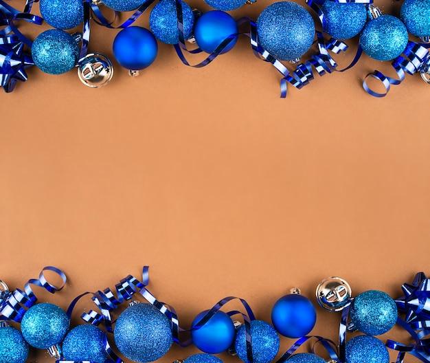 Cornice di natale fatta di palline blu e serpentine su un tavolo marrone. sfondo di natale.