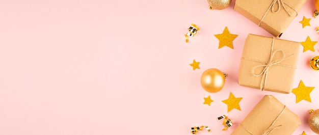 Cornice di natale fatta di palline di natale oro e scatole regalo su uno sfondo rosa.banner.