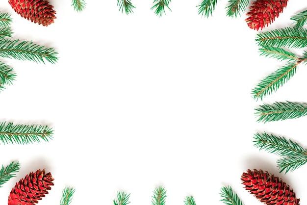 Cornice di natale fatta di coni e rami di abete su sfondo bianco.