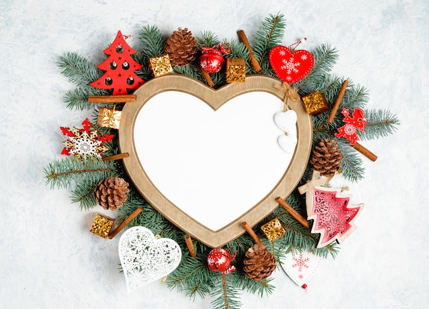 Cornice di natale a forma di cuore, circondata da rami di un albero di natale decorazioni natalizie