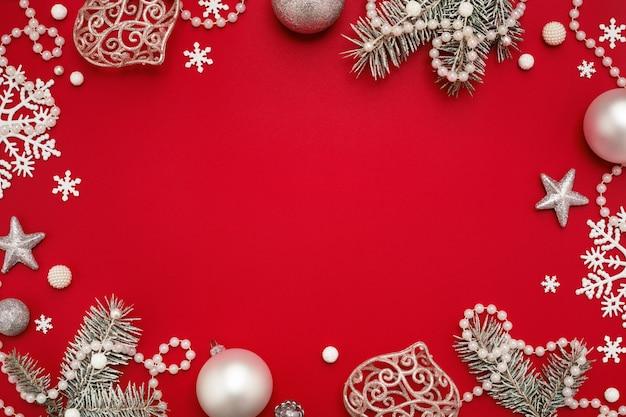 Cornice di natale di ornamenti bianchi su sfondo rosso con spazio di copia.