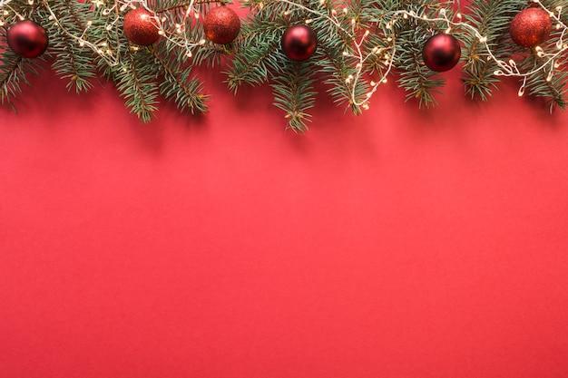 Cornice di natale con rami sempreverdi, palline rosse, ghirlanda su spazio rosso