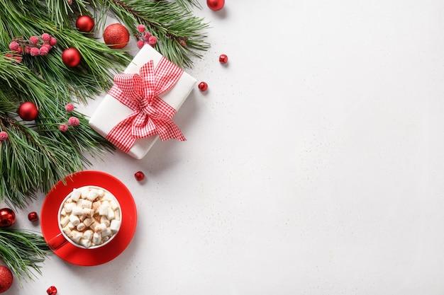 Cornice di natale con regalo, caffè, marshmallow, rami sempreverdi su sfondo bianco con spazio di copia. biglietto di auguri per le vacanze di natale. vista dall'alto, piatto.