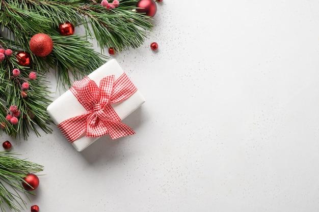 Cornice di natale con regalo, rami di abete su sfondo bianco con spazio di copia. biglietto di auguri per le vacanze di natale. vista dall'alto, disteso.