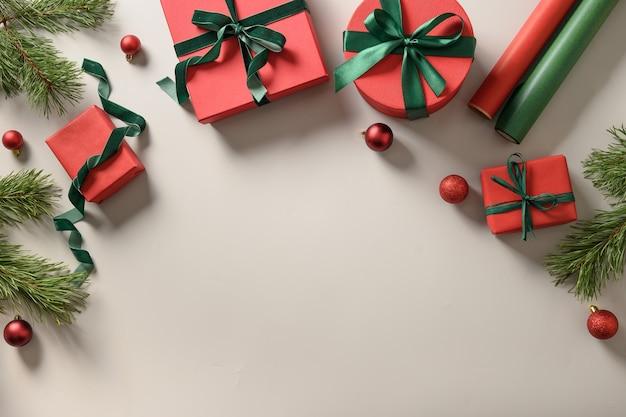 Cornice di natale con regali, palline rosse, rotoli di carta su grigio. preparazione e confezione regalo per le feste. vista dall'alto con copia spazio.