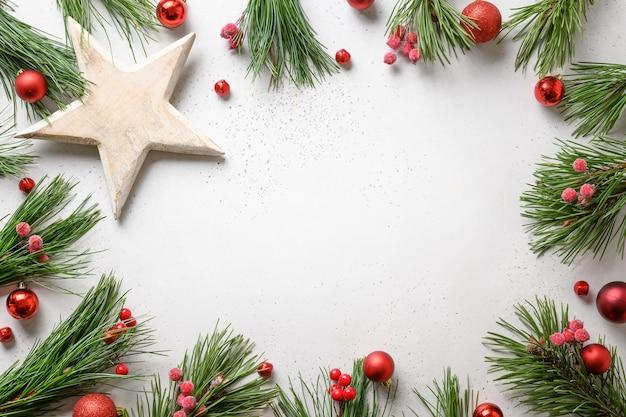 Cornice di natale con decorazioni rosse, stella bianca fai da te su sfondo bianco cartolina d'auguri di festa di natale con lo spazio della copia. vista dall'alto.