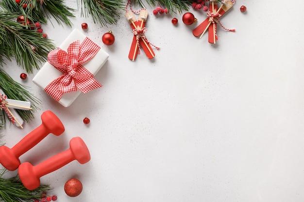 Cornice di natale con manubri rossi e regalo su sfondo bianco con spazio di copia. offerta speciale. vista dall'alto, piatto. fitness, sport e concetto di stile di vita sano.