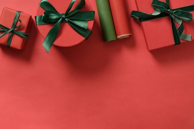 Cornice di natale con doni rossi, rotoli di carta con spazio di copia.