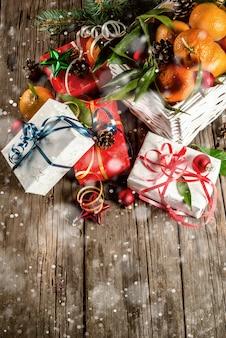 Natale e. mandarini freschi con foglie verdi in un cestino bianco, decorazioni natalizie e scatole regalo, sul vecchio tavolo di legno rustico, vista dall'alto tonica, effetto neve