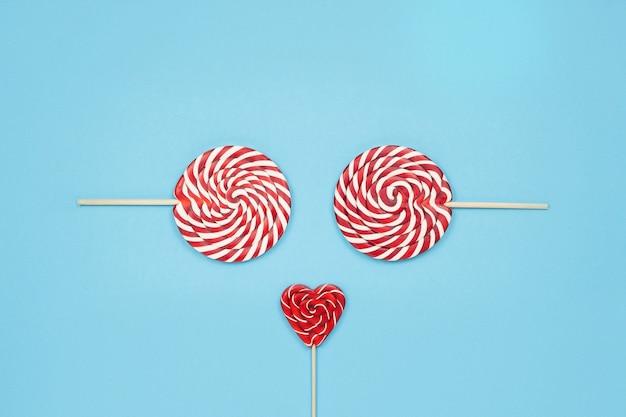 Fronte divertente di natale fatto di lecca-lecca rosso caramelle su sfondo blu