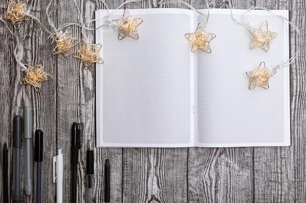 Ghirlanda di natale, quaderno quadrato vuoto, penne su un tavolo di legno grigio