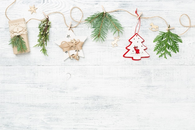 Ghirlanda di natale di rami di conifere e decorazioni natalizie su sfondo bianco.