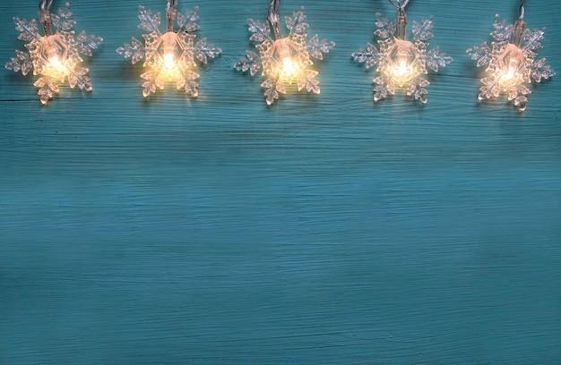 Bordo di luci ghirlanda di natale su un tavolo in legno blu decorazione festiva invernale con spazio di copia