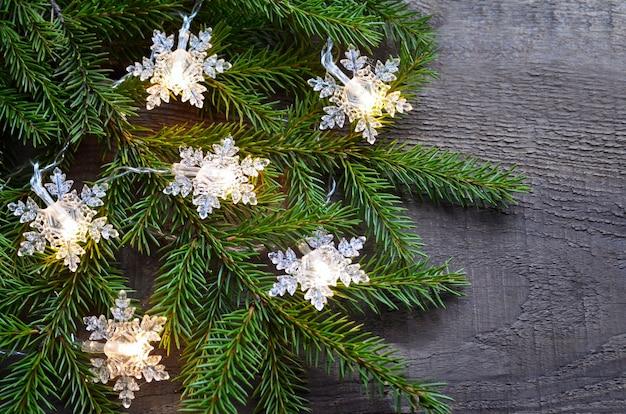 Luci della ghirlanda di natale e ramo di un albero di abete sul vecchio tavolo in legno decorazione festiva invernale