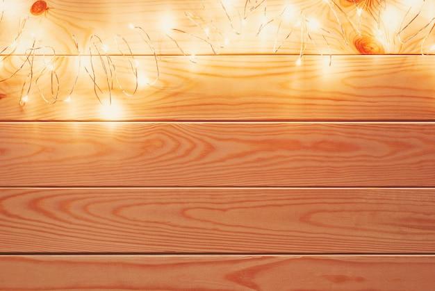 Corda di ghirlanda di natale con luci a led sopra uno sfondo di legno naturale