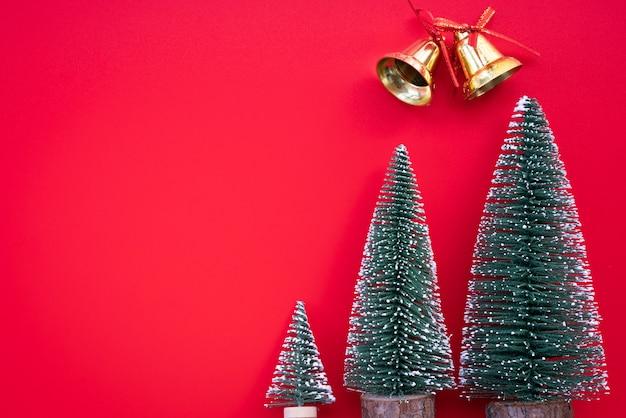 Regalo di natale, campana e albero di pino su sfondo rosso. vista piana, vista dall'alto