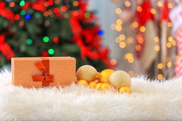 Confezione regalo di natale e palline su soffici plaid su sfondo sfocato