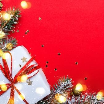 Confezione regalo di natale e rami di conifere con luci su sfondo rosso.