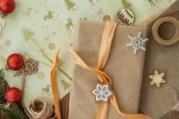Scatola regalo di natale, decorazioni e ramo di un albero di abete sulla tavola di legno. vista dall'alto con copia spazio.