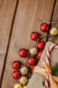 Scatola regalo di natale, decorazioni e ramo di un albero di abete sulla tavola di legno.