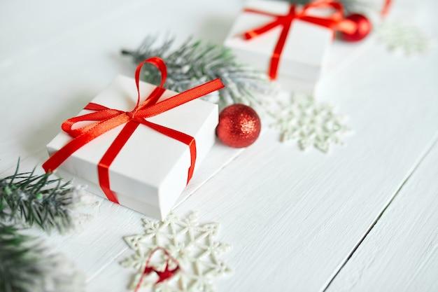 Confezione regalo di natale, rami di abete, decorazioni rosse su fondo di legno bianco, natale, inverno, concetto di capodanno, vista piana, vista dall'alto, spazio di copia