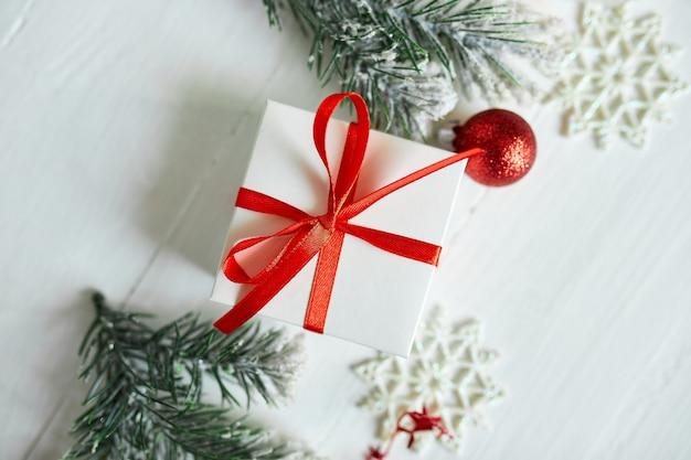 Scatola regalo di natale rami di abete decorazioni rosse su fondo di legno bianco Foto Premium
