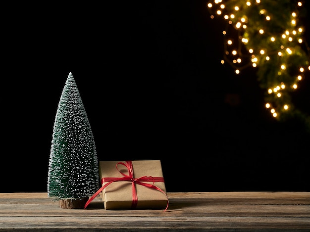Contenitore di regalo di natale e albero di abete sulla tavola di legno contro luci festive sfocate, spazio per testo