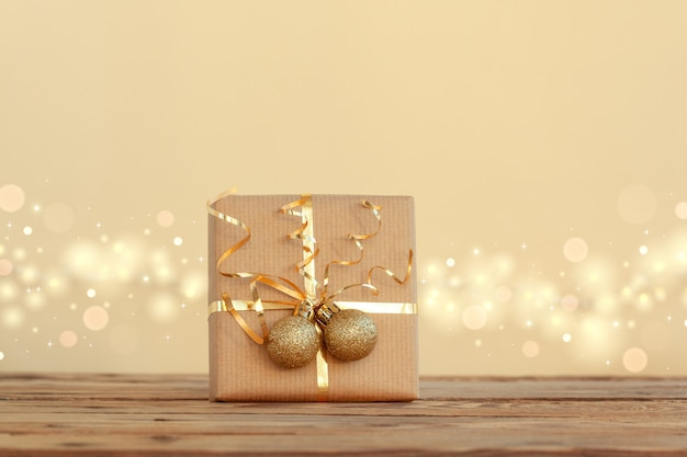 Confezione regalo di natale o regalo decorato con nastro dorato e due palline su sfondo neutro con boke.