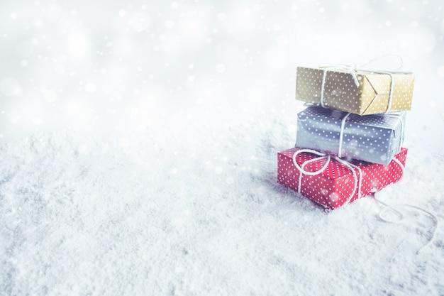 Confezione regalo di natale, presente su sfondo di neve