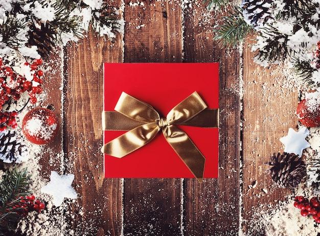 Confezione regalo natalizia presentata nel mezzo di decorazioni natalizie su assi di legno