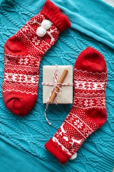 Confezione regalo di natale e calzini rossi, un maglione lavorato a maglia blu e una ghirlanda con coni