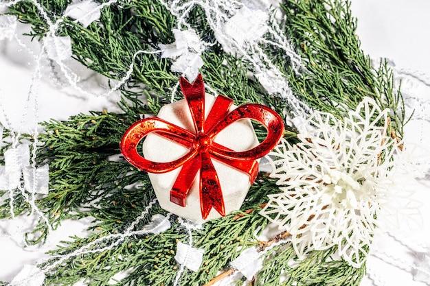 Confezione regalo di natale e fiocco di neve su un ramo di una conifera natale concetto di capodanno