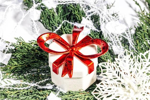 Confezione regalo di natale e fiocco di neve su un ramo di una conifera, natale, inverno, concetto di capodanno.