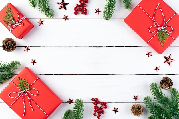 Contenitore di regalo di natale, rami di abete rosso, pigne, bacche rosse su fondo di legno.