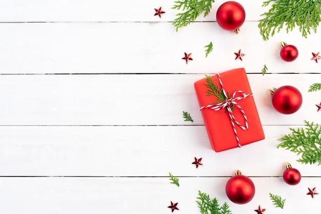 Contenitore di regalo di natale, rami di abete rosso, palla rossa su fondo di legno