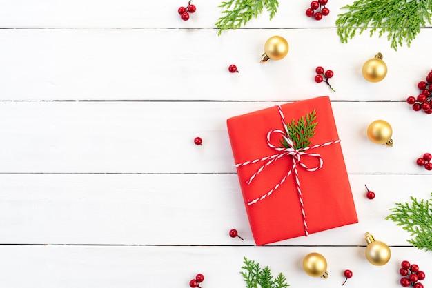 Contenitore di regalo di natale, rami di abete rosso, bacche rosse su fondo di legno.