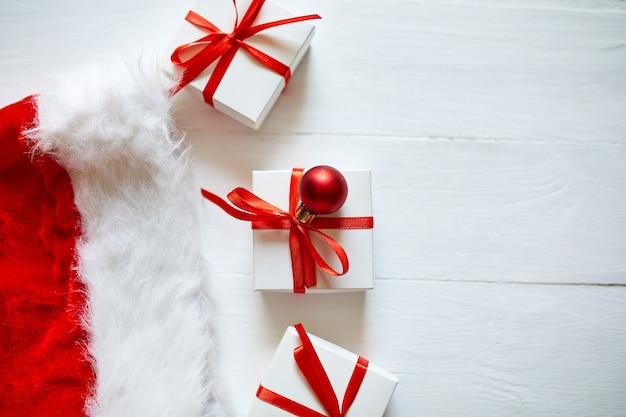 Confezione regalo di natale wit cappello da babbo natale, decorazioni rosse su fondo di legno bianco, natale, inverno, concetto di capodanno,