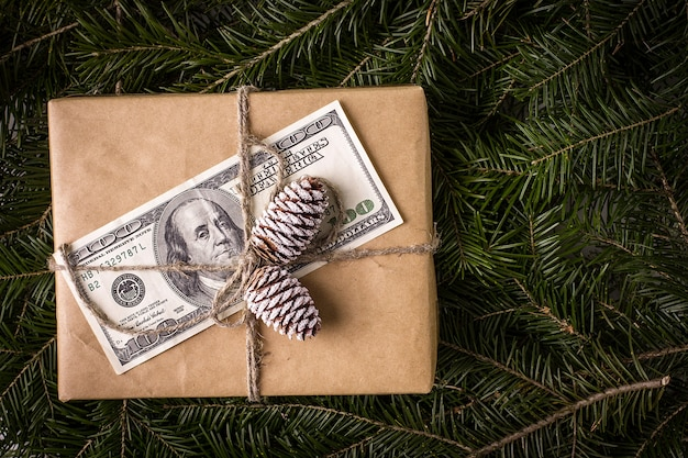 Contenitore di regalo di natale con la banconota del dollaro. biglietto natalizio